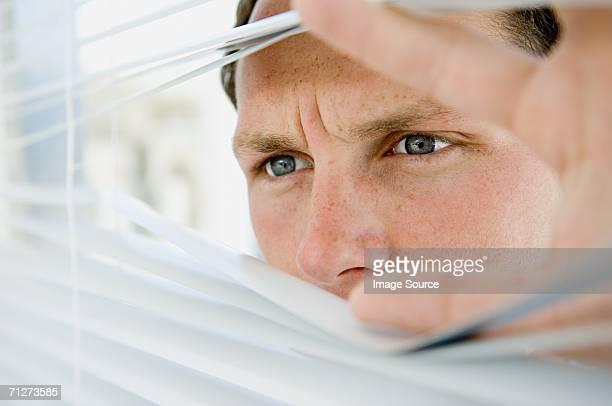 Businessman looking through blinds