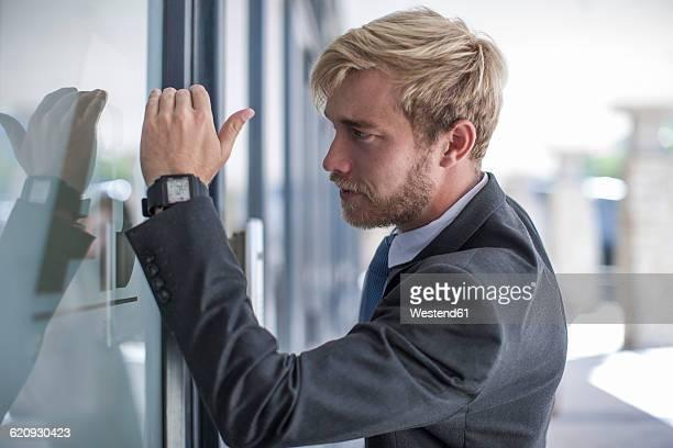 Businessman looking through glass door