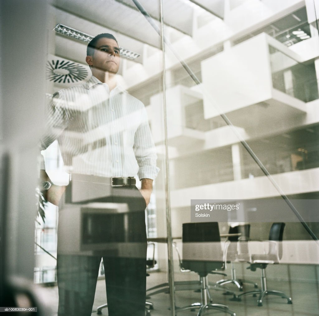Businessman looking through office glass wall, low angle view : Stock Photo