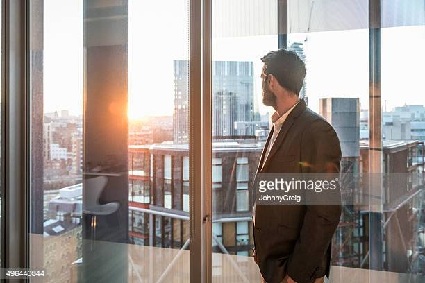 businessman looking through office window in sunlight - looking through window stock pictures, royalty-free photos & images