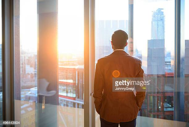 businessman looking through office window in sunlight - verandering stockfoto's en -beelden