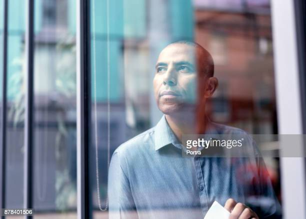 businessman looking through office window - looking through window stock photos and pictures