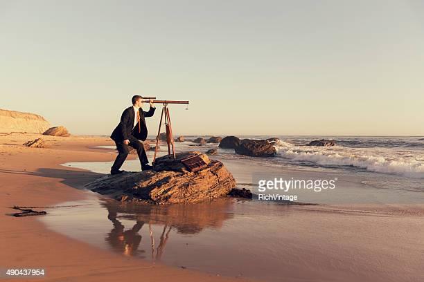 Geschäftsmann mit Fernglas am Strand, Kalifornien