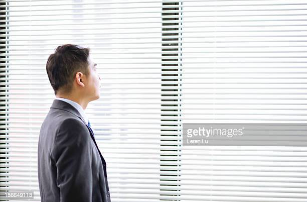 businessman looking through venetian blinds - leren stock pictures, royalty-free photos & images