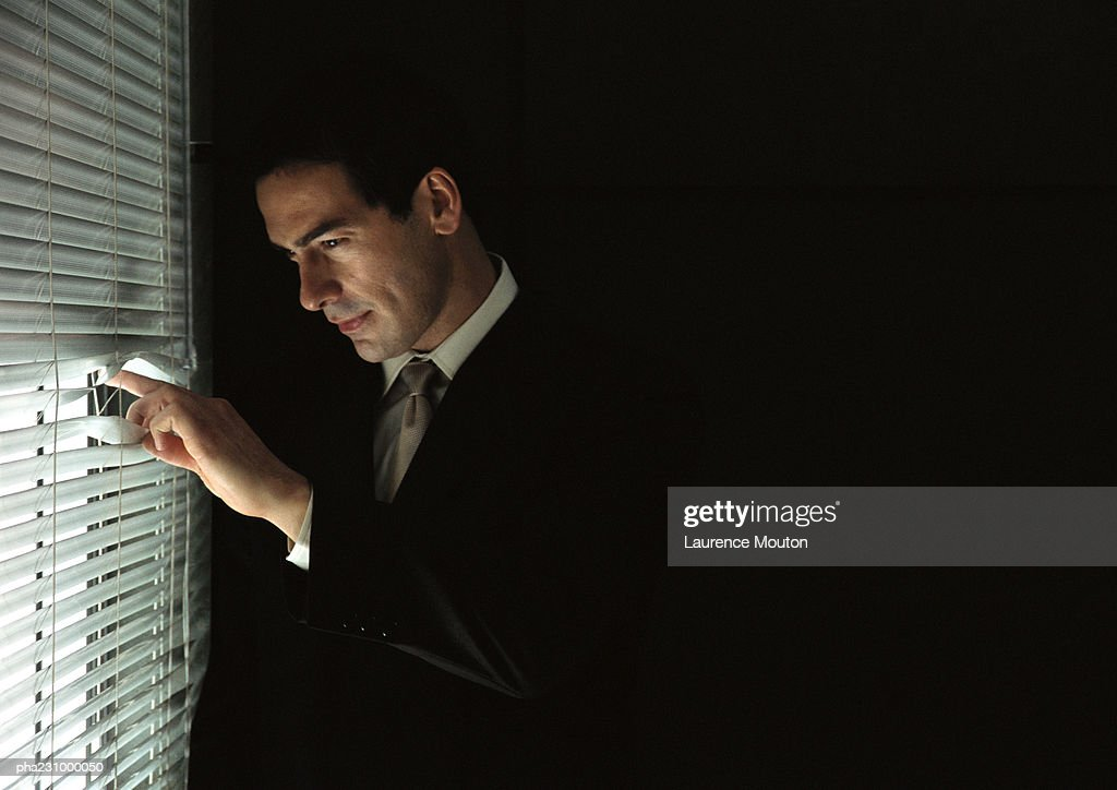 Businessman looking through venetian blinds, portrait : Stock Photo
