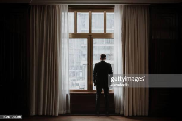 都市景観の美しい窓を通して見る実業家 - geschäftsmann ストックフォトと画像