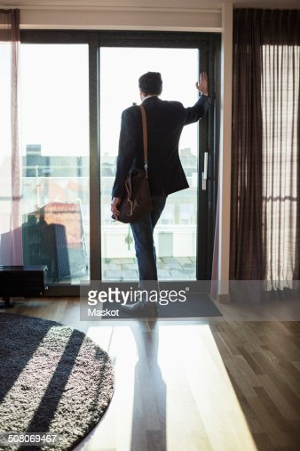 Hotel Room Photography: Businessman Looking Through Window In Hotel Room Stock