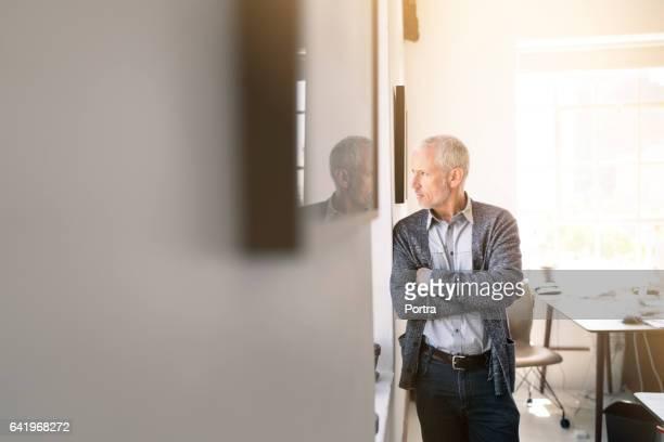 empresário olhando pela janela do escritório - só um homem maduro - fotografias e filmes do acervo