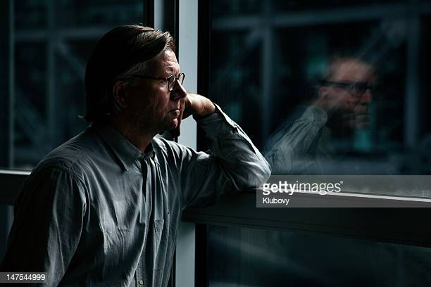 businessman looking through window - ongerust stockfoto's en -beelden