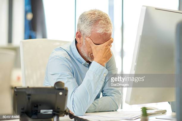 Businessman looking tired in real office location