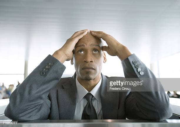 Businessman looking up and holding head in airport