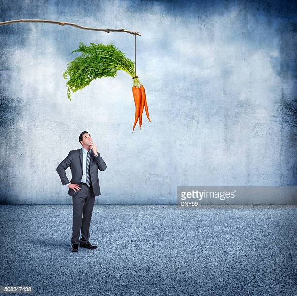 businessman looking up at a carrot dangling from a stick - incentive stock photos and pictures