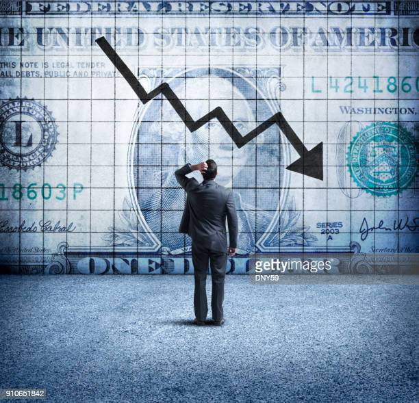 businessman looking up at a chart that indicates a falling u.s. dollar - crisi foto e immagini stock