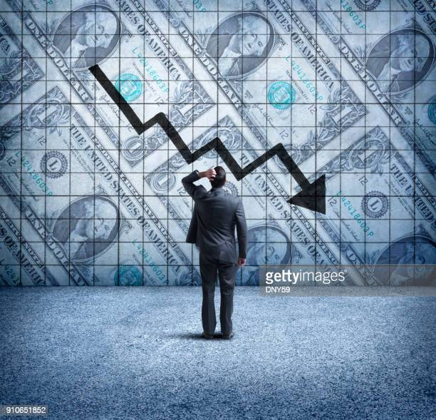 Businessman Looking Up At a Chart That Indicates A Falling U.S. Dollar
