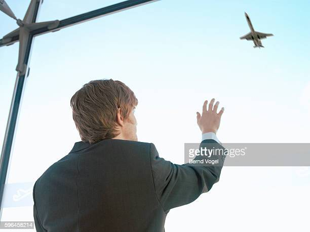 Businessman looking up at a jet airplane