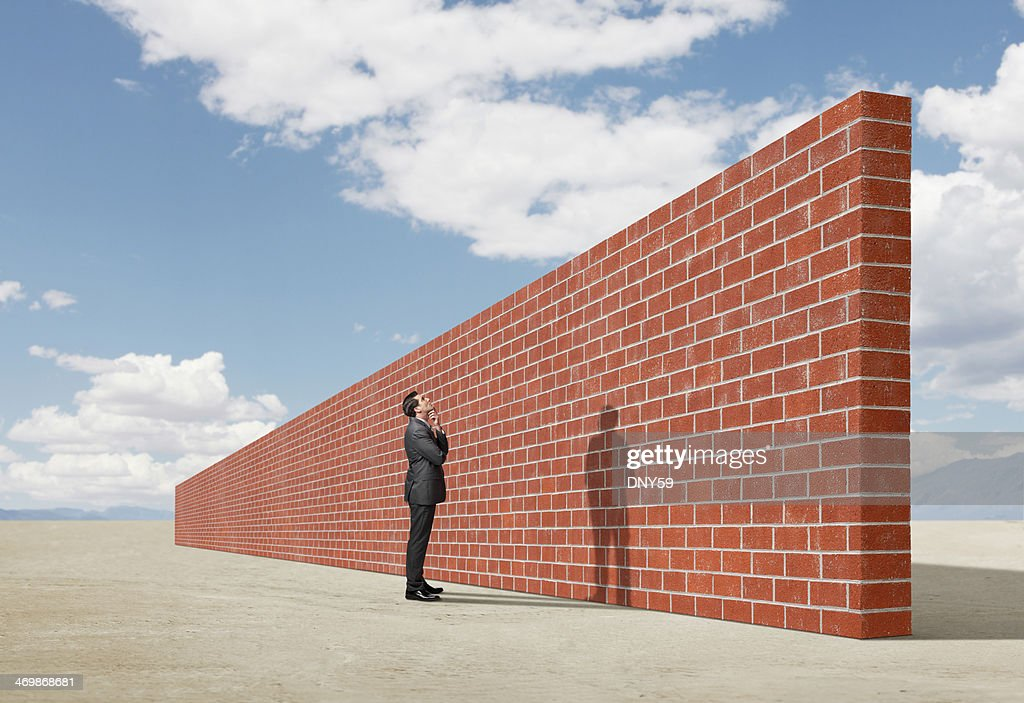 Businessman looking up at brick wall in middle of desert : Stock Photo