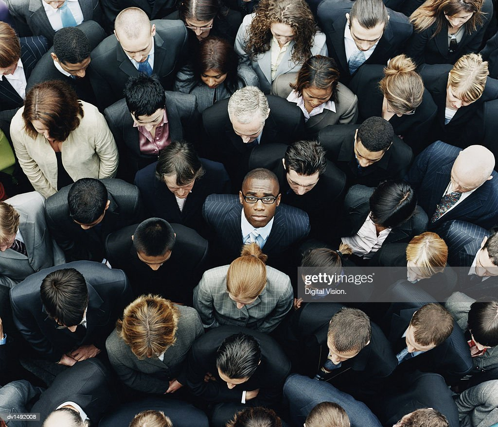 Businessman Looking up at Camera and Standing Outdoors Surrounded by a Large Group of Business People : Stock Photo