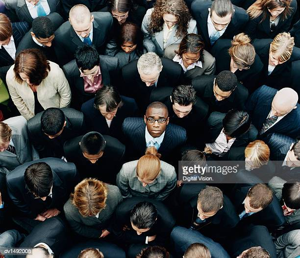businessman looking up at camera and standing outdoors surrounded by a large group of business people - individuality stock pictures, royalty-free photos & images