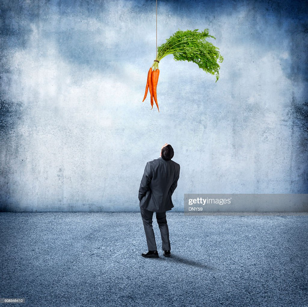 Businessman Looking Up At Carrots Dangling Above Him : Stock Photo