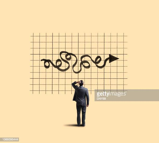 businessman looking up at chart showing unpredictable moves - capitalism stock pictures, royalty-free photos & images