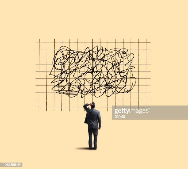 businessman looking up at chart showing unpredictable moves - economia foto e immagini stock