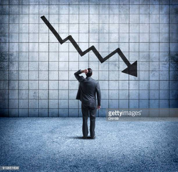 businessman looking up at downward trending arrow with concern - decline stock pictures, royalty-free photos & images
