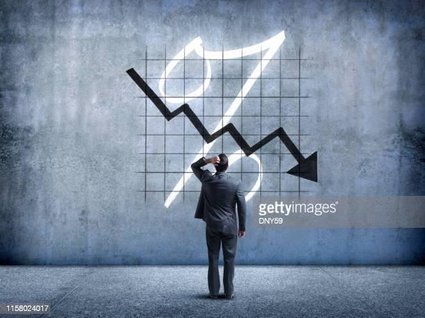 homem de negócios que olha acima em taxas de juros de queda - caindo - fotografias e filmes do acervo