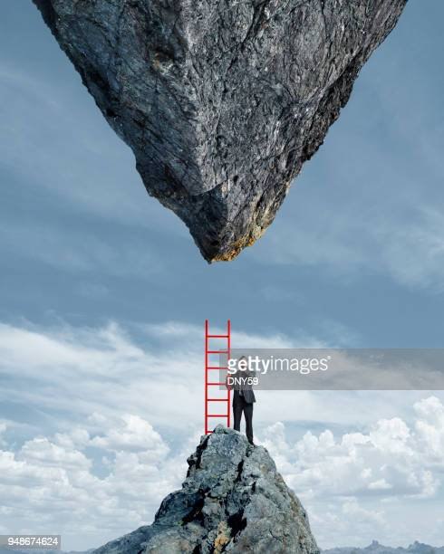 businessman looking up at impossible task - adversidade imagens e fotografias de stock