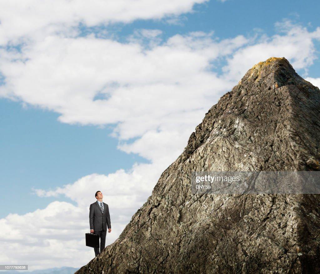 Businessman Looking Up At Mountain Peak : Stock Photo