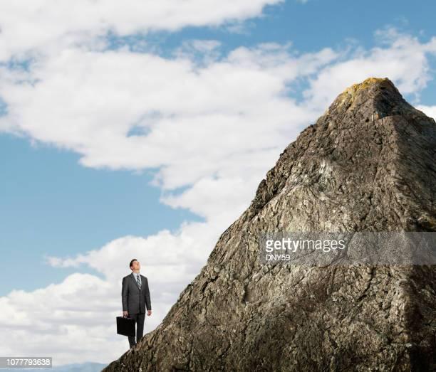Homme d'affaires à la recherche de haut au sommet de la montagne