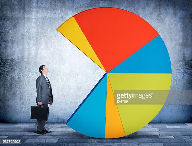 Businessman Looking Up At Pie Chart With Missing Piece