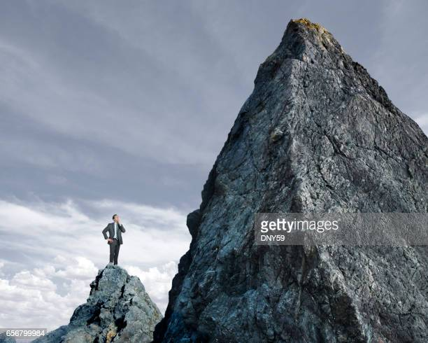 businessman looking up at tall mountain - steep stock photos and pictures
