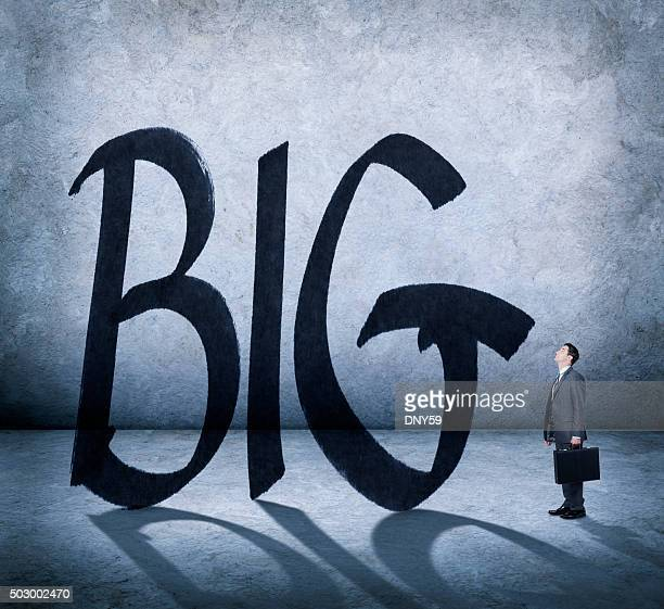 Businessman Looking Up At The Word 'Big'