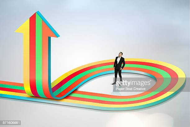 businessman looking up at winding colorful arrow
