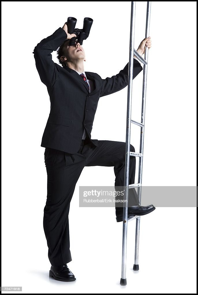 Businessman looking up corporate ladder with binoculars : Stock-Foto