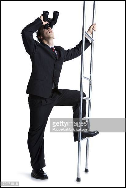 Businessman looking up corporate ladder with binoculars