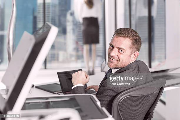 Businessman looking up from laptop in office
