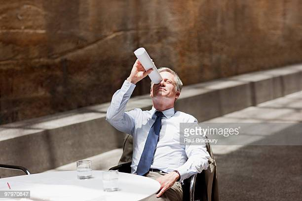 businessman looking up through rolled up paperwork - wasting time stock pictures, royalty-free photos & images
