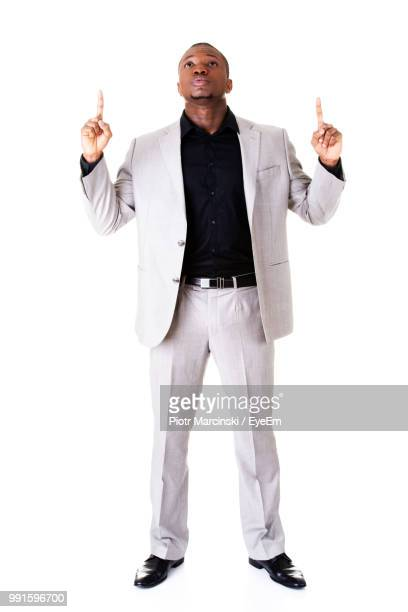 businessman looking up while standing against white background - one man only stock pictures, royalty-free photos & images
