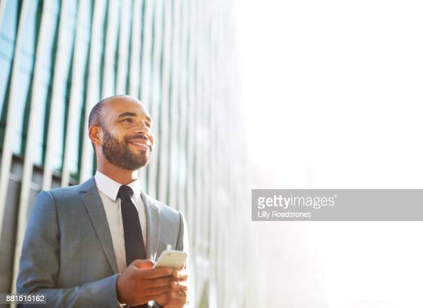 Businessman looking up while using mobile phone in modern city environment
