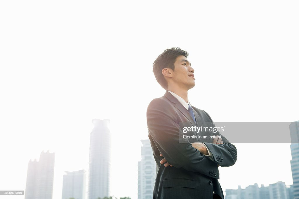 Businessman looking up with arms folded : ストックフォト