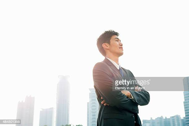 Businessman looking up with arms folded