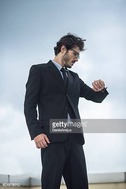 businessman looking what is the time on his watch