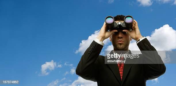 Businessman looking with binoculars.