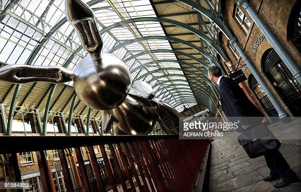 A businessman looks at a giant inflatable rabbit balloon in Covent Garden in central London on October 8 2009 US artist Jeff Koons' rabbit has been...