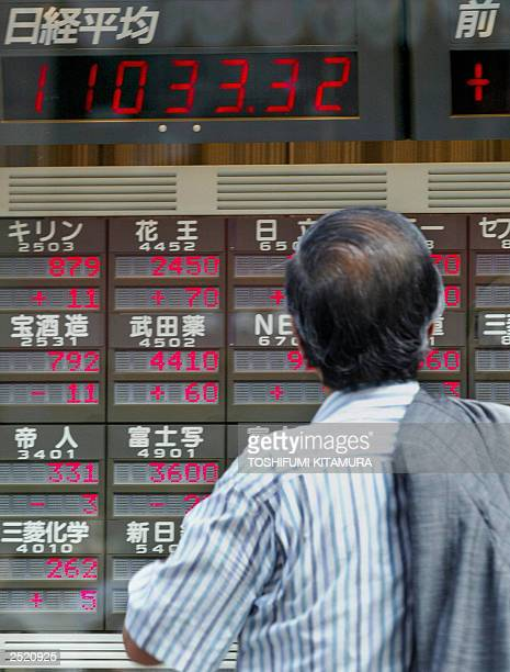 Businessman looks at an electronic stock quotation board in central Tokyo, 18 September 2003, as the indicator flashes its close at 11,033.32. The...