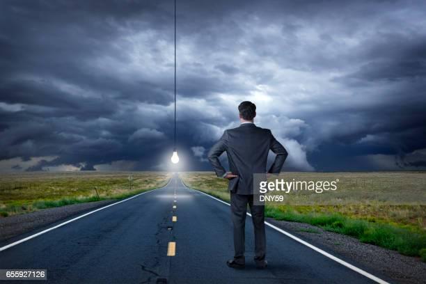 Businessman Looks At Lightbulb Illuminating Long Straight Rural Road