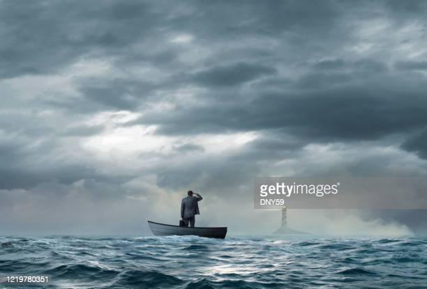 businessman looks at lighthouse while stranded on boat - rough stock pictures, royalty-free photos & images