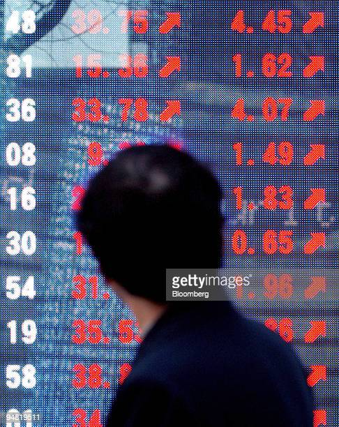A businessman looks at the closing prices of Japanese stocks on a display in downtown Tokyo Thursday January 19 2006 Japan's Topix index staged the...