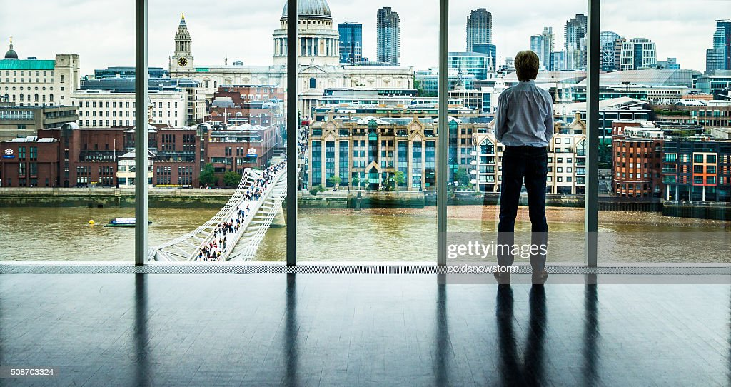 Businessman looks at the London Skyline from his Office Window : Stock Photo